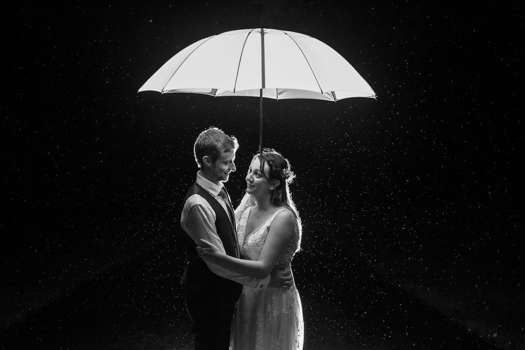 Bride and Groom Under an Umberella in the rain at Rudding park
