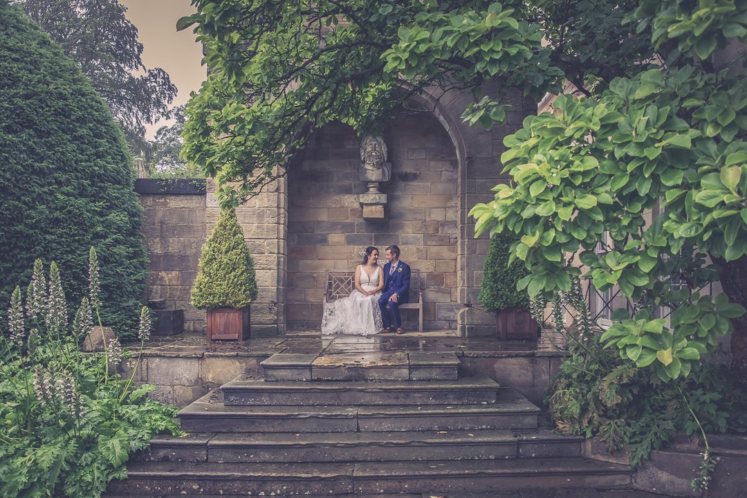 Bride and Groom sitting on a bench at Rudding Park
