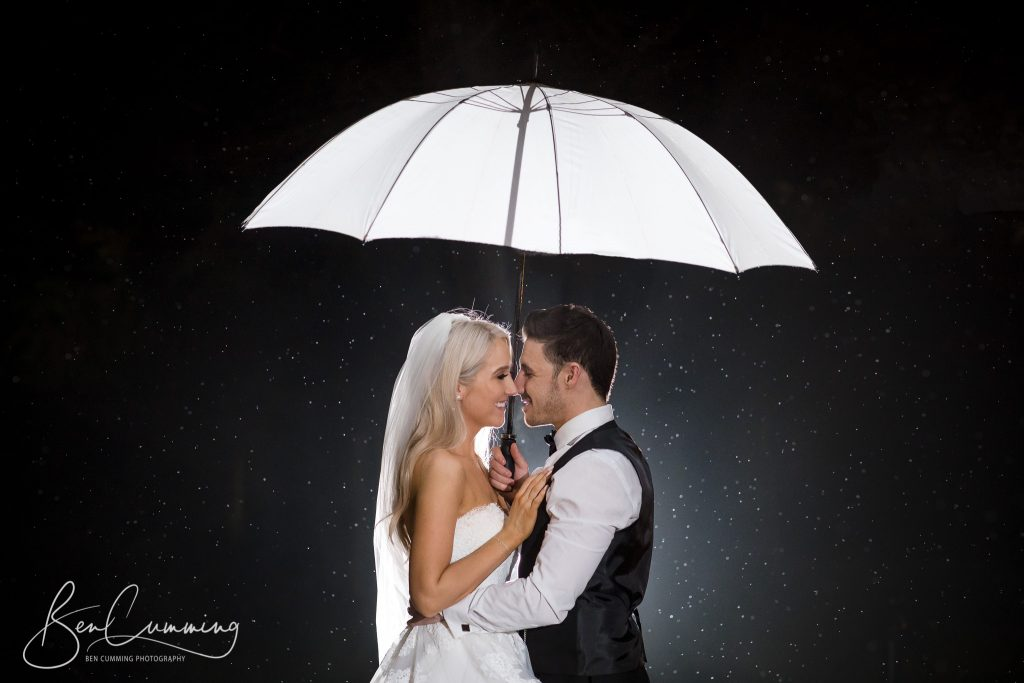 The Bride and Groom under an umbrella at Oulton Hall