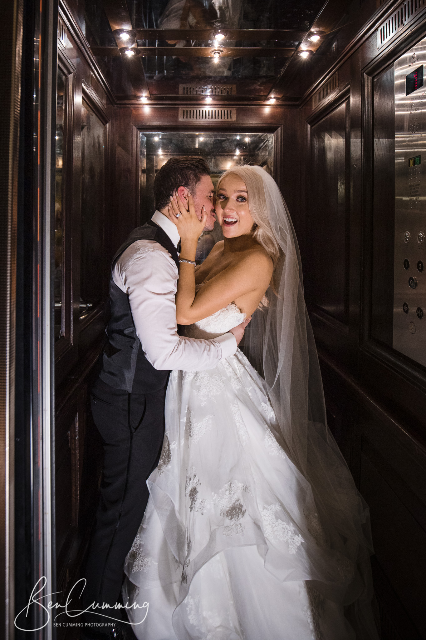 The bride and groom in a lift at Oulton Hall